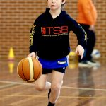 A boy playing basketball at School holiday basketball camp July 2019